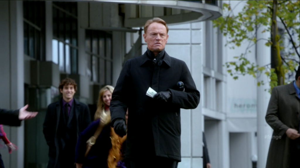 David Robert Jones (Jared Harris) handing out money