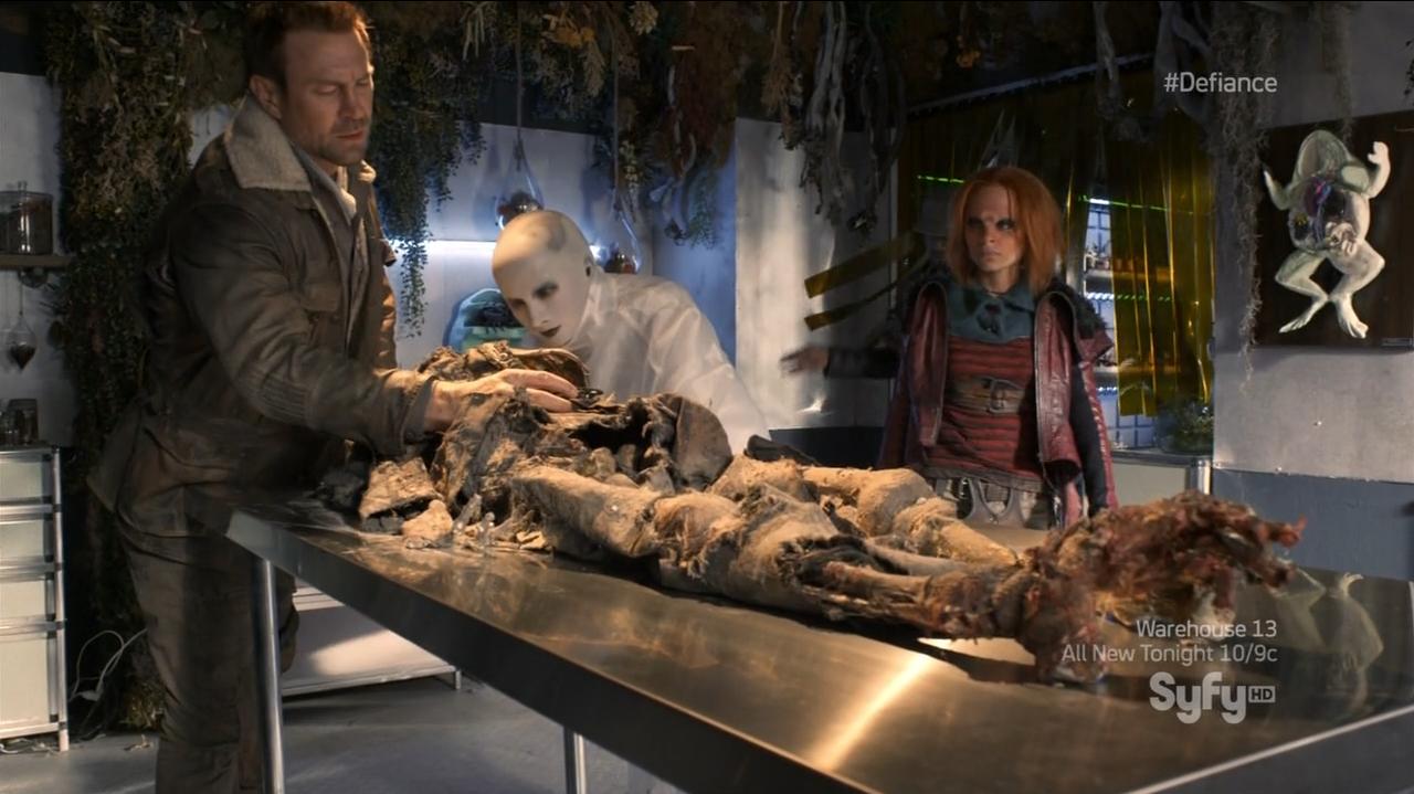 Nolan investigating the dead body - Defiance