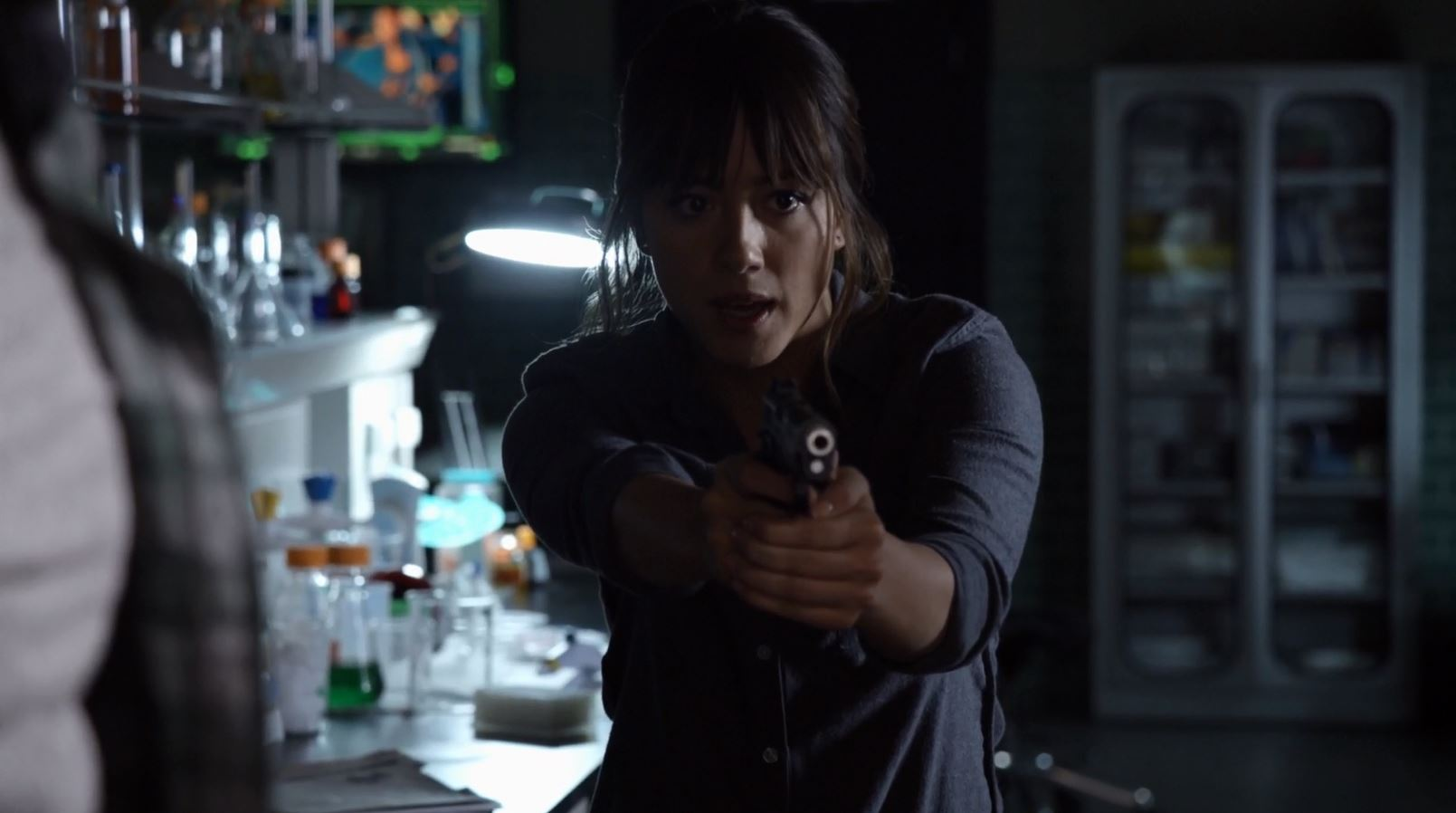 Chloe Bennet as Skye points a gun at Coulson - Agents of SHIELD The Writing on the Wall Review