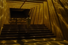 Luv-wearing-white-pencil-skirt-ascending-Wallace-Corp-staircase-basking-in-gold-light