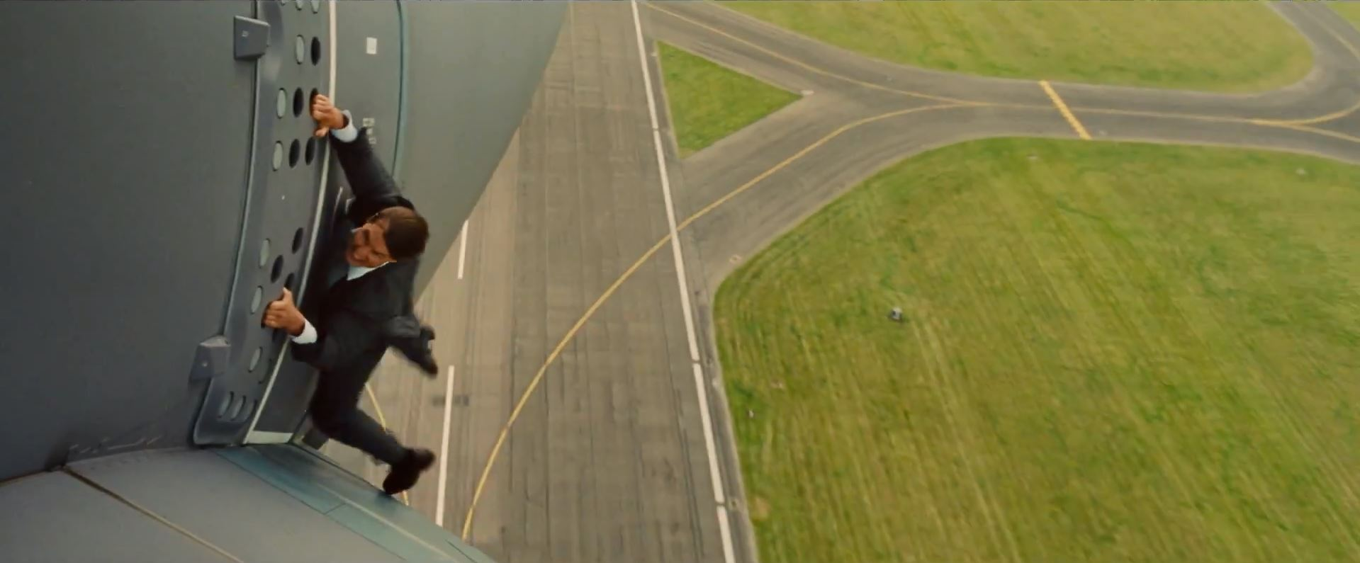 Ethan Hunt (Tom Cruise). Hanging from an aircraft.
